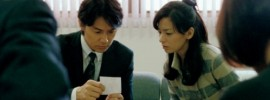Masaharu Fukuyama and Machiko Ono look at a photo of their biological son in 'Like Father, Like Son'